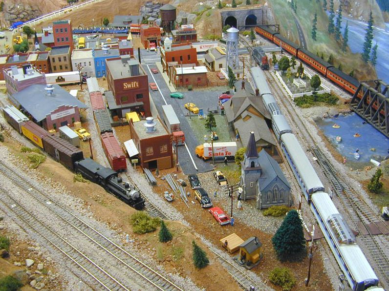 A well designed model railroad that includes a small town, multiple trains and tracks with realistic layouts, and a bit of countryside along with a body of water.